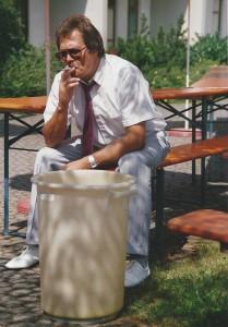 Herr  Kollmann rauchend mit Mülltonne